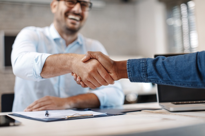 man smiling shaking hands