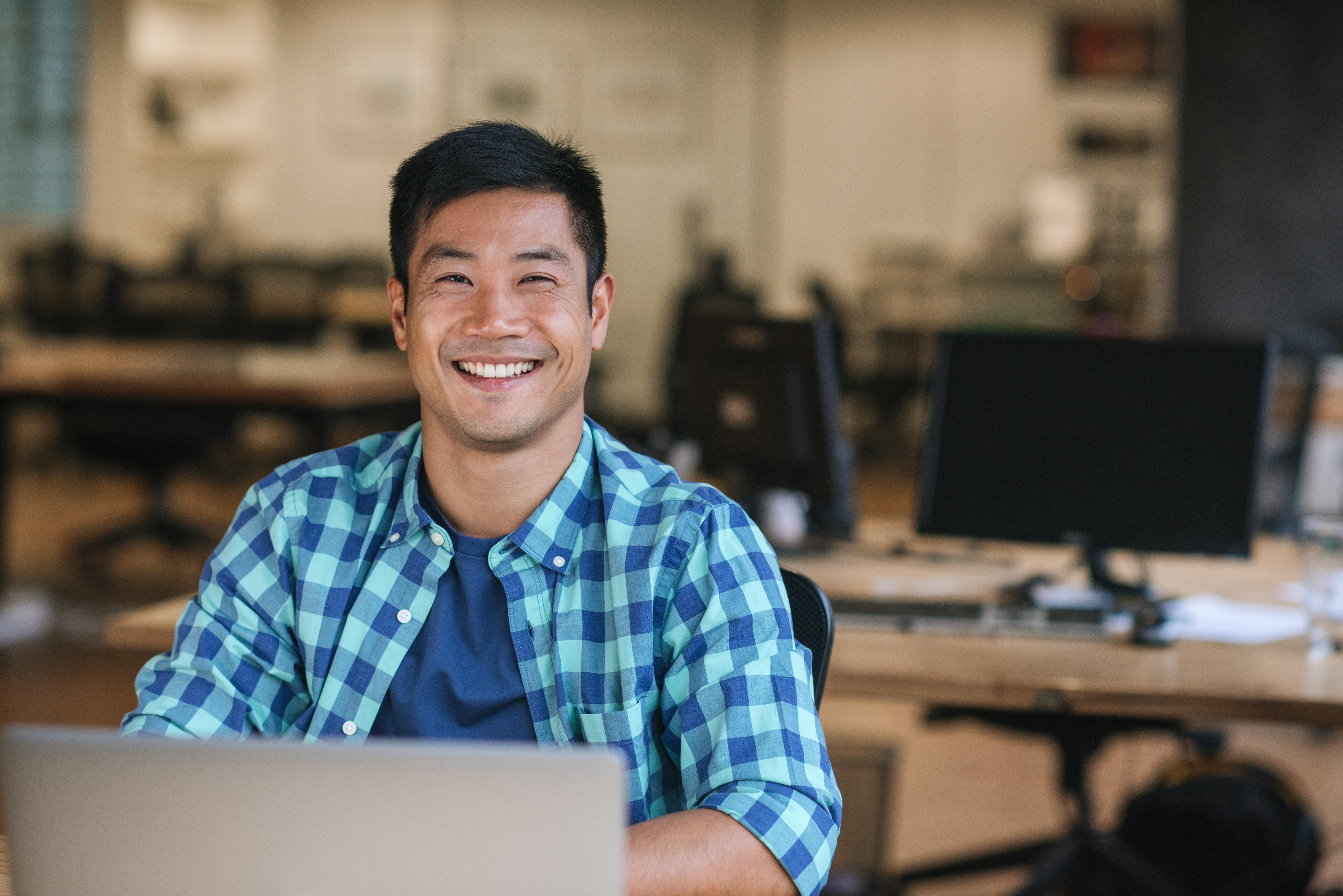 man smiling looking up from laptop