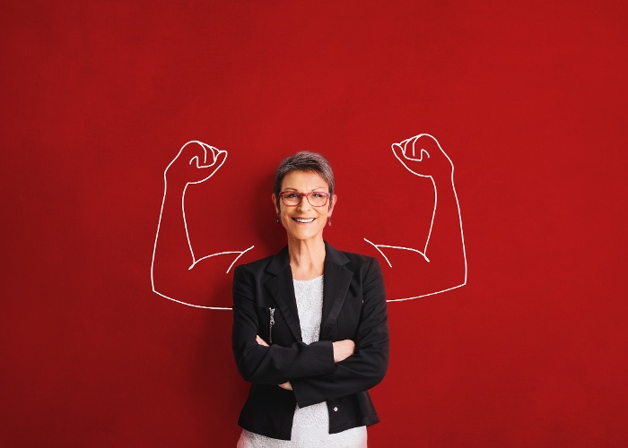 woman with cross arms standing in front of muscular arms on a red background