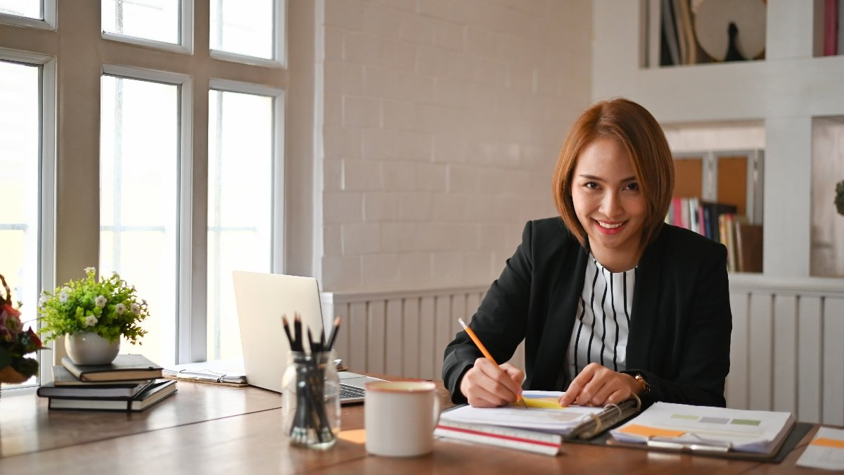Lady smiling and working at desk