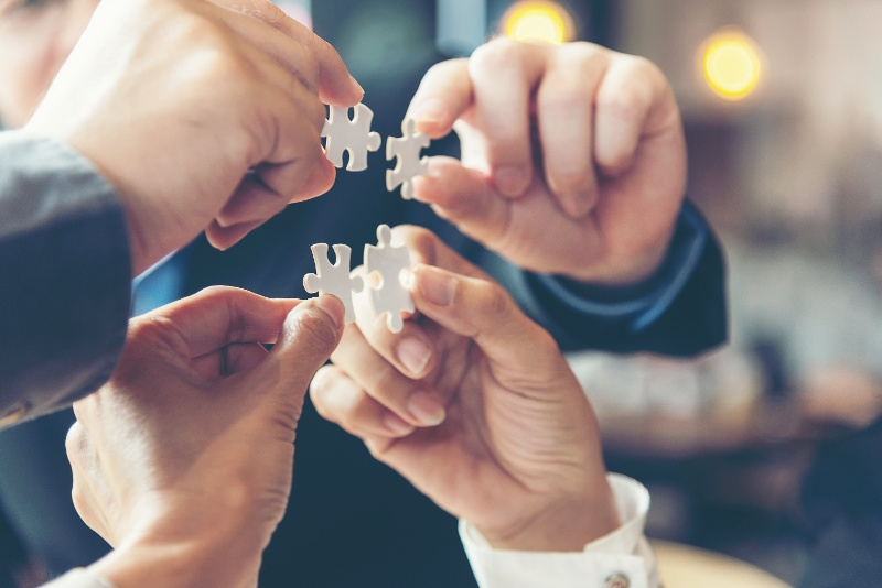 group of hands holding puzzle pieces together