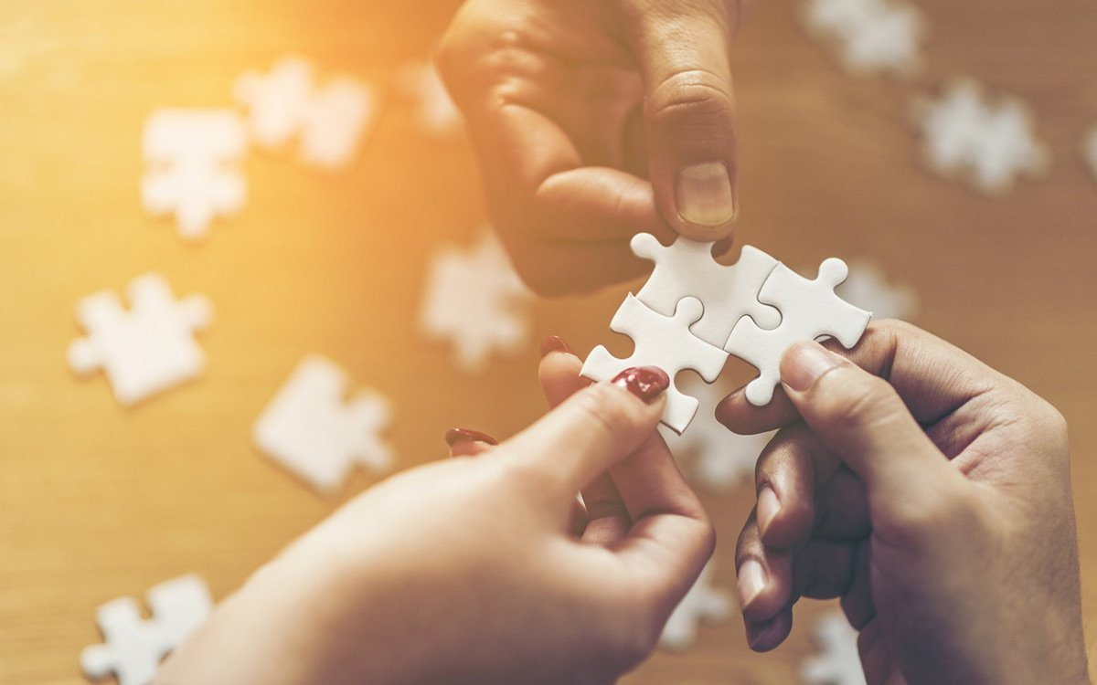 multiple hands holding puzzle pieces together